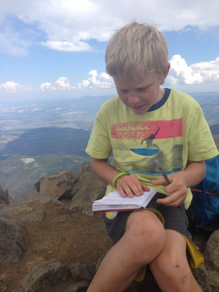 Recent homeschool day. Writing in a journal on top of a 14,000 ft peak.